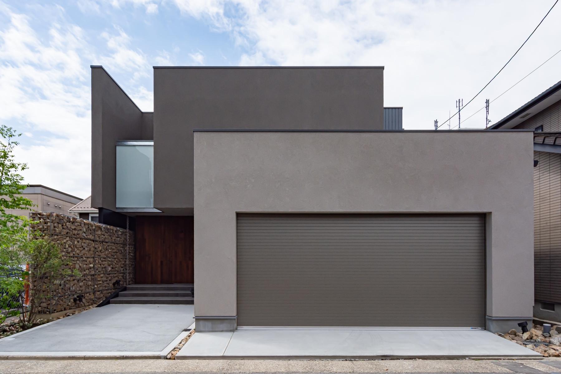車2台が余裕で駐車できるインナーガレージのある邸宅、ガビオンを建物に取り込んだ大胆な外観を提案